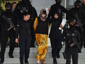 Doan Thi Huong (C) is escorted by Malaysian police from court