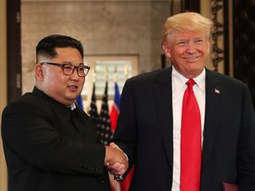 U.S. President Donald Trump and North Korea's leader Kim Jong Un shake hands after signing documents during a summit at the Capella Hotel on the resort island of Sentosa, Singapore June 12, 2018
