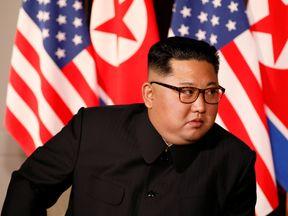 Kim Jong Un listens to U.S. President Donald Trump