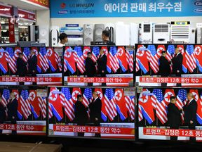 Donald Trump and Kim Jong Un's historic meeting as seen on TV screens at a retail store in Seoul