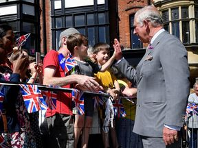 Prince Charles gives a high five during his visit