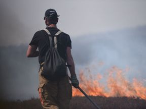 A firefighter uses a beater to help stop the fire spreading on Saddleworth Moor. Pic: Manchester Fire