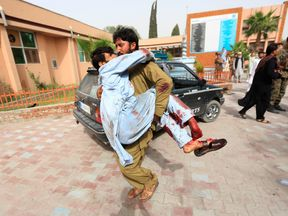 An injured man is carried to a hospital after a car bomb in Jalalabad city, Afghanistan June 17, 2018
