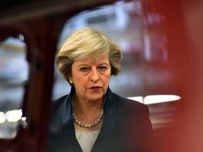 Theresa May views a car on a production line during a visit to the Jaguar Land Rover factory