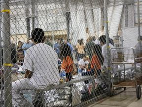 People sit in cages in the facility