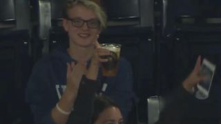 Woman catches baseball ball in her beer