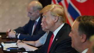Donald Trump smiles as he looks at Kim Jong Un from across the table