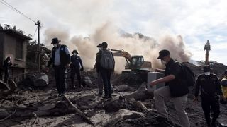 Police officers search for victims of the Fuego Volcano eruption