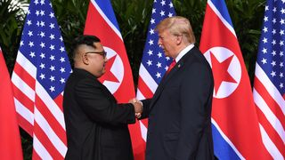 North Korea's leader Kim Jong Un (L) shakes hands with US President Donald Trump (R) at the start of their historic US-North Korea summit, at the Capella Hotel on Sentosa island in Singapore on June 12, 2018. - Donald Trump and Kim Jong Un have become on June 12 the first sitting US and North Korean leaders to meet, shake hands and negotiate to end a decades-old nuclear stand-off