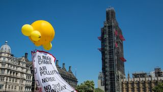 Greenpeace activists fly a banner as they demonstrate against plans to build a third runway at Heathrow