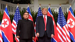 Messrs Trump and Kim pose at the first ever summit between sitting leaders of the US and North Korea