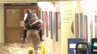 Firefighters give piggybacks at flooded station