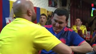 A Colombian man helps a blind and deaf fan experience the joy of their team's World Cup campaign