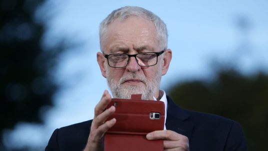 Jeremy Corbyn takes a picture with an smartphone at a rally on the eve of Labour conference in Brighton