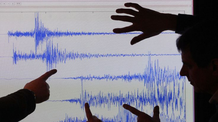 Staff at the British Geological Survey survey a graph showing a UK earthquake in 2008