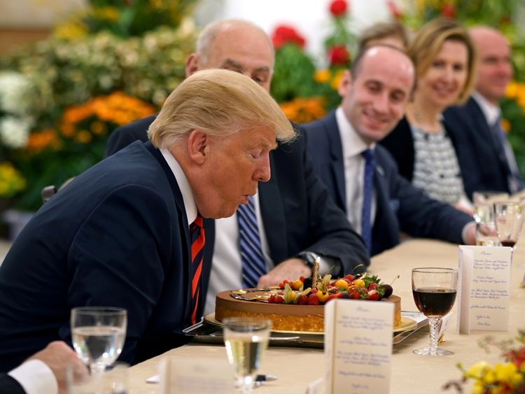 Donald Trump blows out the candle on his birthday cake