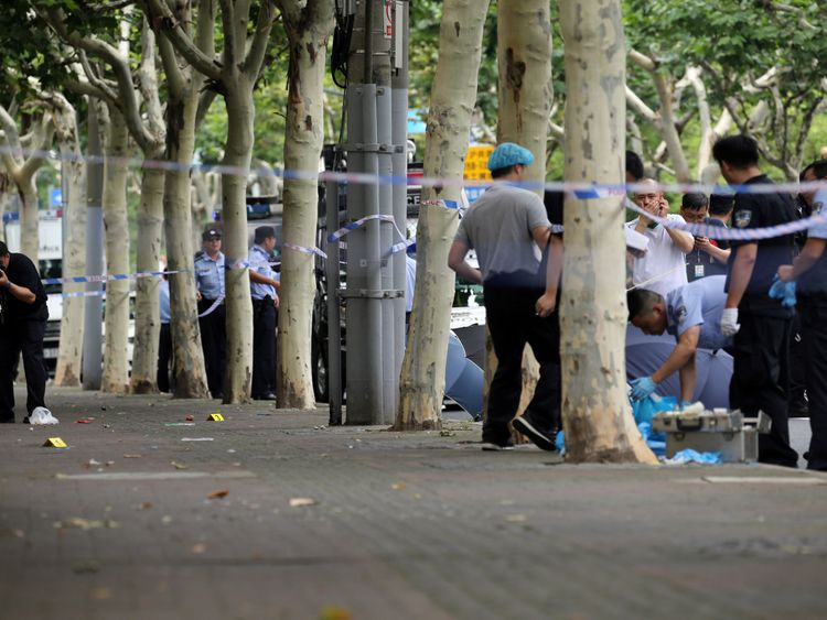 Police officers work at the scene after a man armed with a knife attacked students at the entrance to a primary school