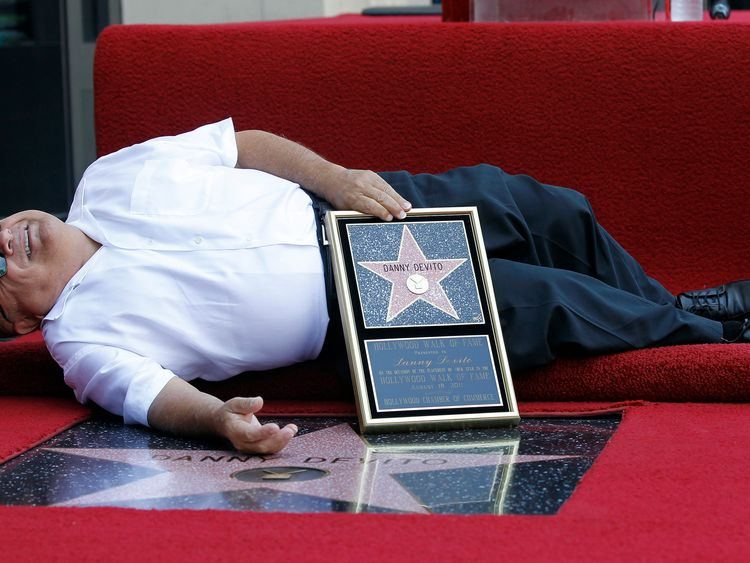 Actor Danny DeVito lies down by his star