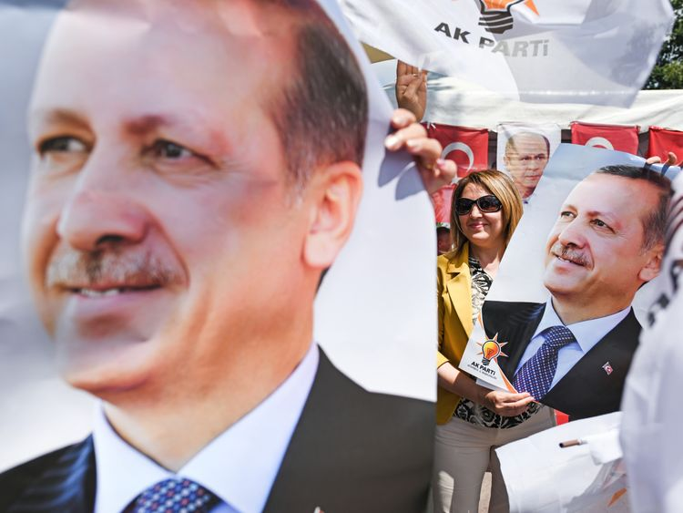 People hold posters of Mr Erdogan during a rally on 20 June