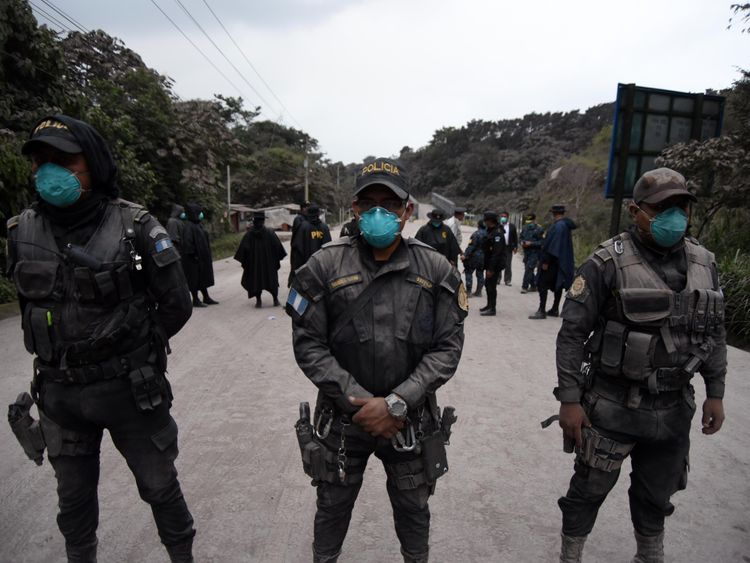 Police officers are posted, as the Fuego Volcano erupts