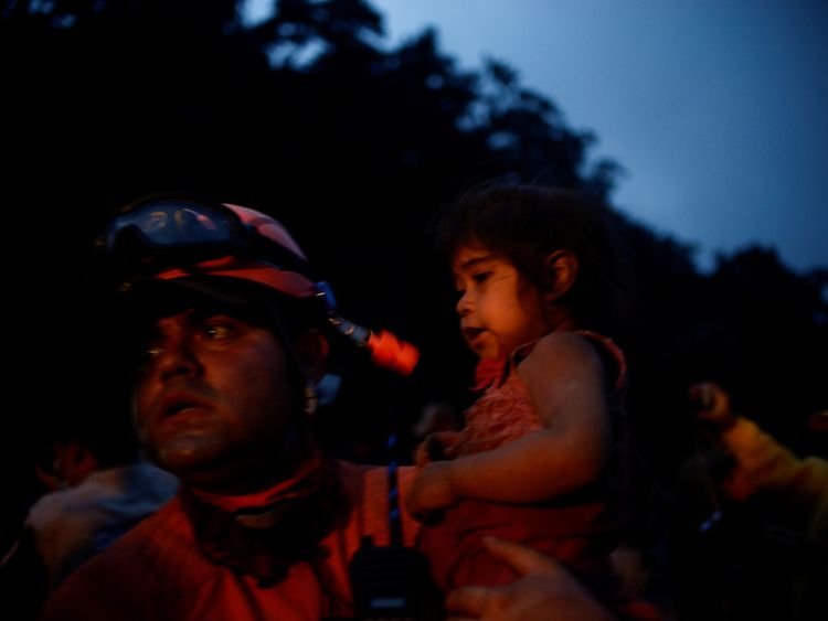 A rescue worker holds a little girl covered with ash following the eruption