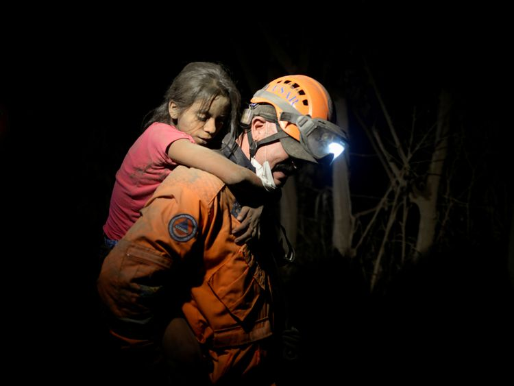 A rescue worker carries a child through the darkness to safety