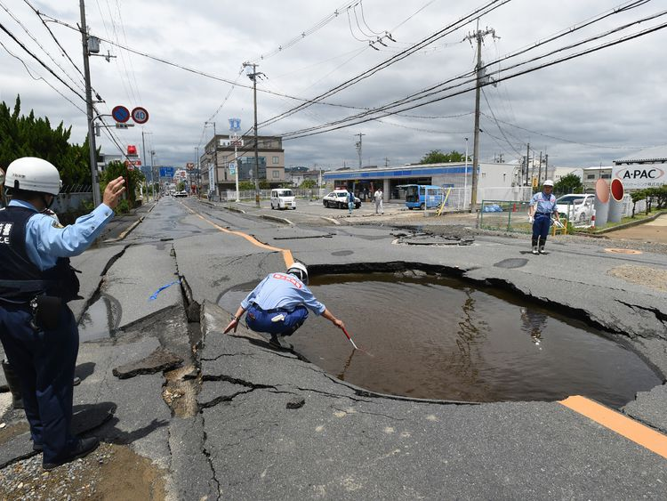 Police check a collapsed road following an earthquake in Takatsuki, north of Osaka, Japan