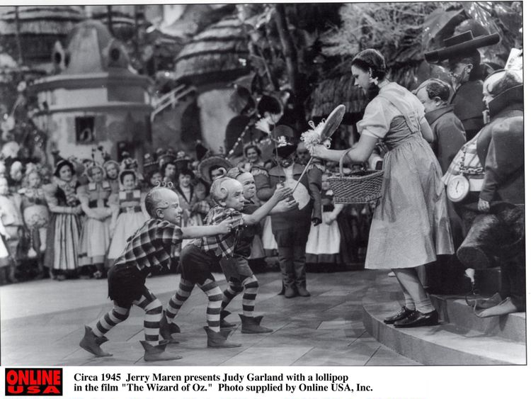 Jerry Maren presents Judy Garland with a lollipop in the film The Wizard of Oz.