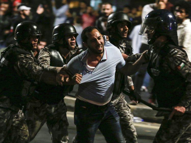 Members of the Jordanian gendarmerie detain a protester