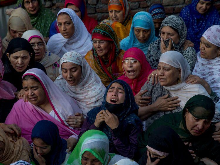Kashmiri women grieve near the body of Qaiser Amin Bhat, during his funeral