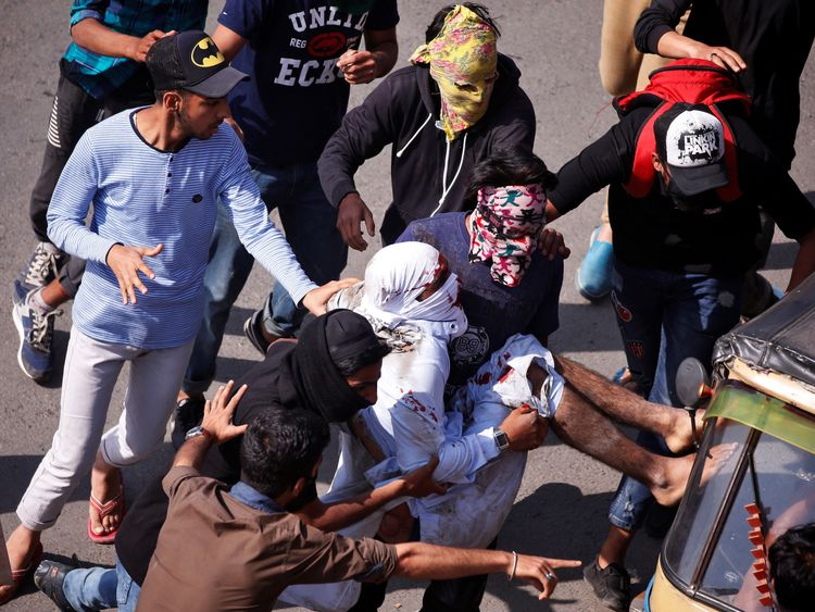 Protesters carry an injured man who was hit by a Central Reserve Police Force (CRPF) vehicle