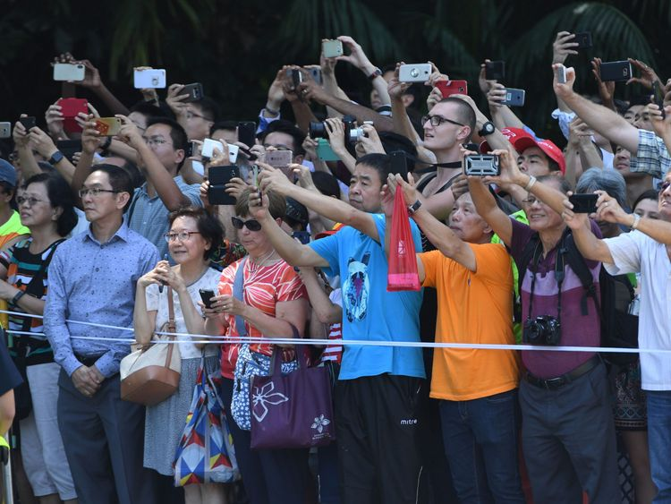ystanders look on and take pictures of the motorcade transporting US President Donald Trump (not pictured) as it drives towards the Istana, the official residence of the Singaporean prime minister