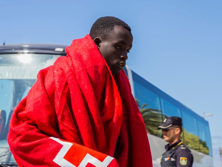 A migrant, part of a group intercepted aboard a make-shift boat at sea south of Spain's Canary Islands, is escorted by Spanish police after arriving in Maspalomas, on the island of Gran Canaria