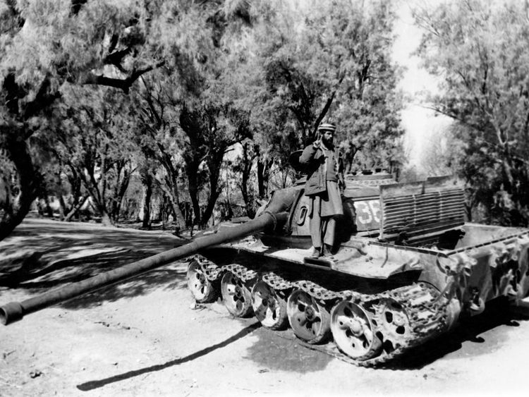 A mujahideen fighter stands on a captured Soviet tank in February 1989