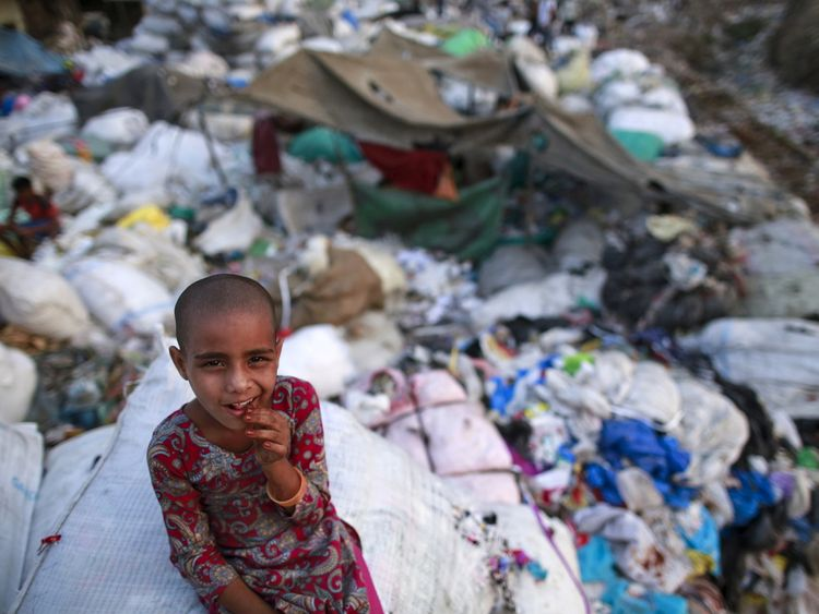 A girl sits among discarded rubbish in a Mumbai slum