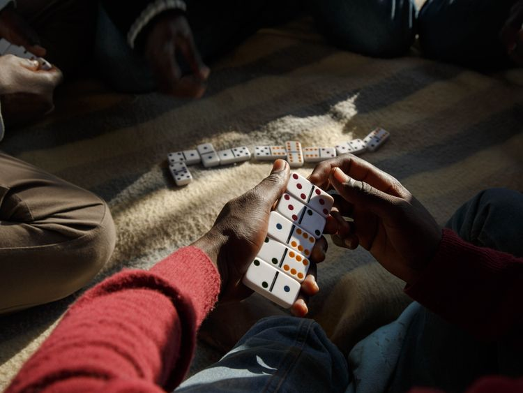 Migrants playing dominoes under a flyover in Ventimiglia. Pic: Oxfam/Agostino Loffredi