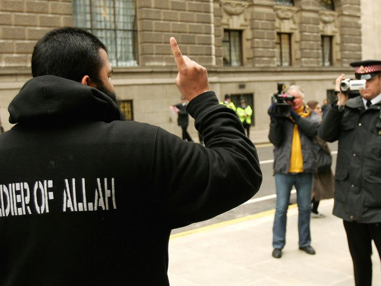 LONDON - FEBRUARY 07: A supporter of the controversial Muslim cleric Abu Hamza al-Masri is filmed by a British police officer as he protests outside of the Old Bailey criminal court on February 7, 2006 in London, England. Hamza has been found guilty of inciting murder and race hate and jailed for seven years. (Photo by Scott Barbour/Getty Images)