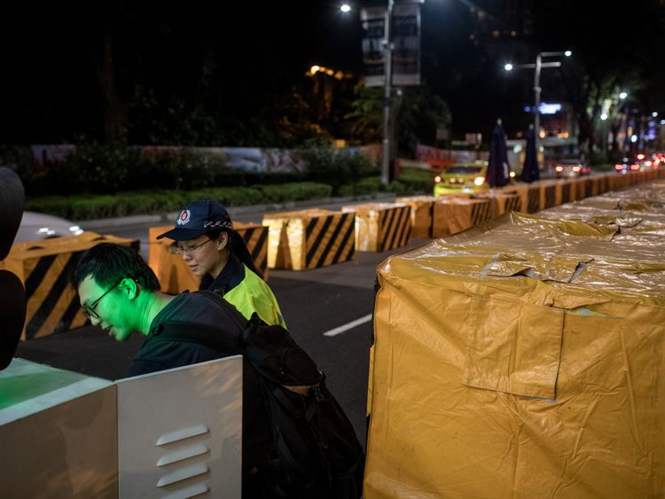 A man sets up an electronic security gate at a vehicle checkpoint in front of the St. Regis Hotel