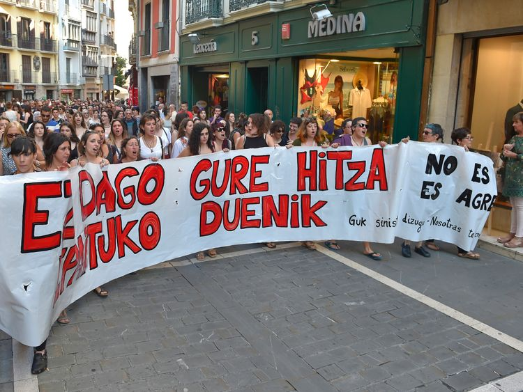 Demonstrators hold a banner reading: 'There is no one who judges our word - it is not abuse, it is aggression'