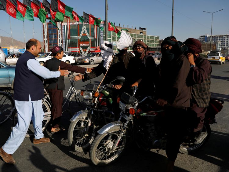 Taliban on motorbikes shake hands with Afghans in Kabul