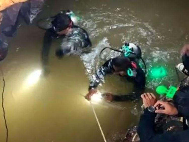Divers making their way through water in the tunnels of the complex