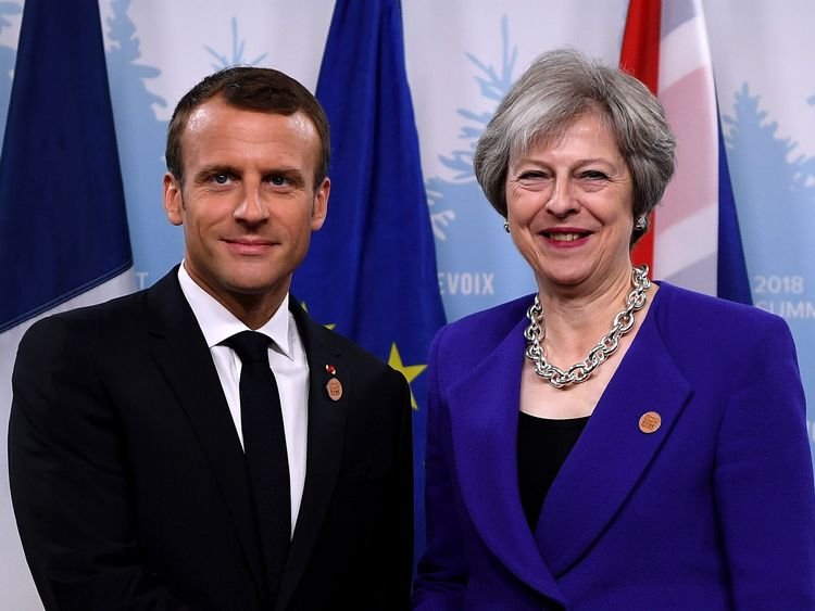 Theresa May poses for a photo with French President Emmanuel Macron on day one of the G7 meeting in Quebec, Canada
