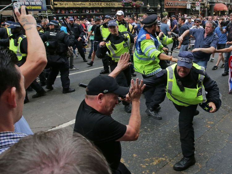 Protesters scuffle with police on Whitehall during a gathering by supporters of far-right spokesman Tommy Robinson in central London on June 9, 2018, following the jailing of Tommy Robinson for contempt of court. (Photo by Daniel LEAL-OLIVAS / AFP) (Photo credit should read DANIEL LEAL-OLIVAS/AFP/Getty Images)