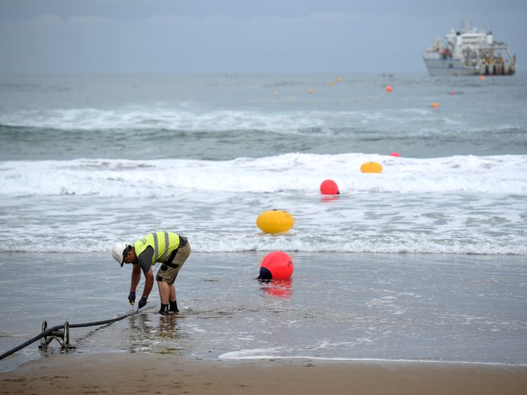 An operator works during the mooring of an undersea fiber optic cable at Arrietara beach near the Spanish Basque village of Sopelana on June 13, 2017. Facebook and Microsoft have paired up to run a giant underwater cable dubbed Marea (tide) that will stretch from Virginia in the US to Bilbao, Spain, crossing some 6,600 kilometers of ocean. / AFP PHOTO / ANDER GILLENEA (Photo credit should read ANDER GILLENEA/AFP/Getty Images)