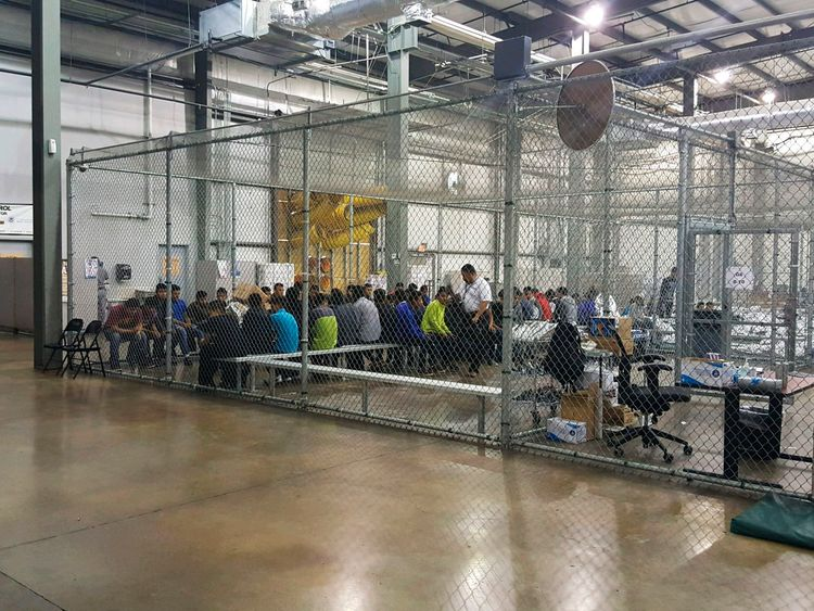 People sit on benches inside a cage in the facility