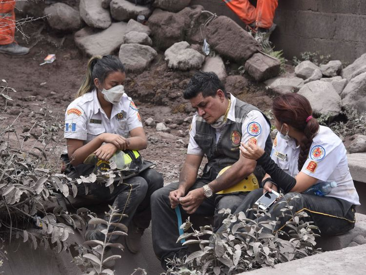 Emergency service staff take a break during the exhausting search for survivors