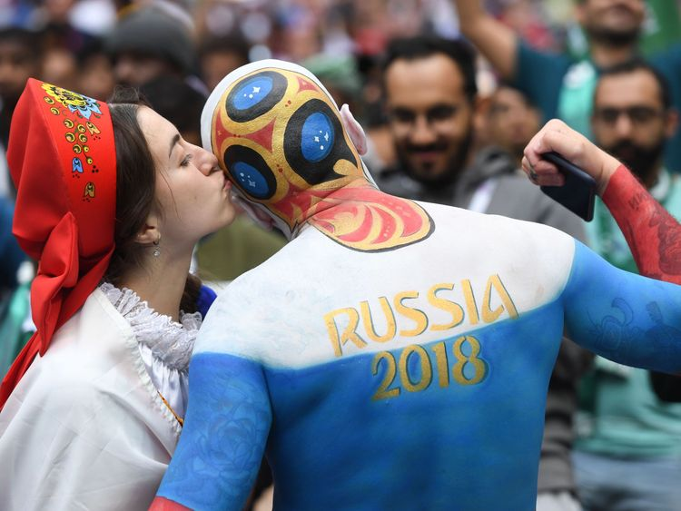 A Russia fan kisses another supporter before the start of the Russia 2018 World Cup Group A football match between Russia and Saudi Arabia at the Luzhniki Stadium in Moscow