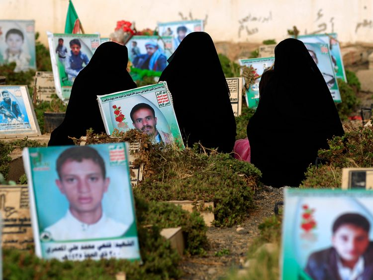 Yemenis visit the graves of relatives at a cemetery in Sanaa on 15 June