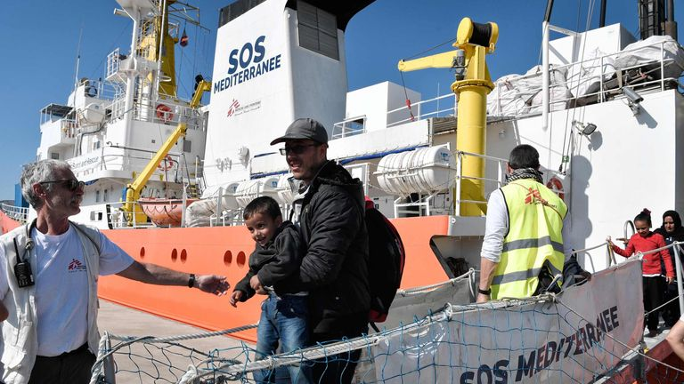 A migrant and his child disembark from the MV Aquarius last month