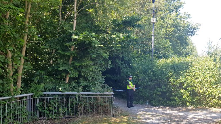A policeman stands guard next to a path that is cordoned off, as it leads to the stretch of the River Aire in Leeds, where a teenage swimmer died after getting into difficulty in the water